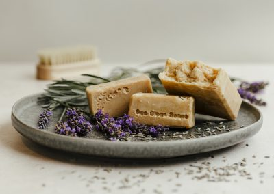 Selection of lavender soap bars on plate with lavender scattered around
