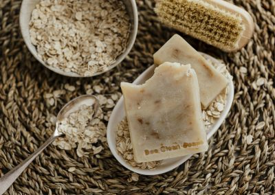 Close up of soap bar products with oatmeal scattered around