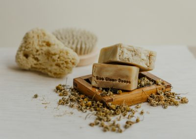 Close up of two natural soap bar with chamomile scattered around