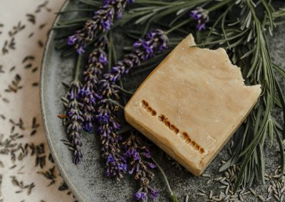 Close up of lavender soap bar on plate with lavender scattered around