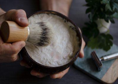 Man holding coconut bowl of shaving cream