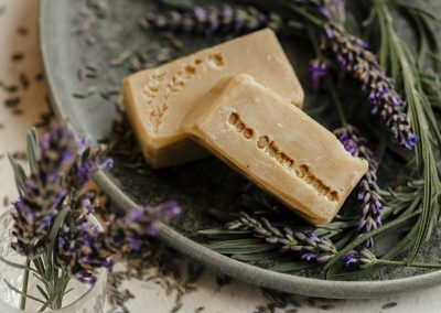 Close up of lavender soap bar products on plate with lavender scattered around