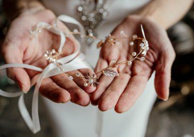 Brides hands holding metallic hair piece accessory